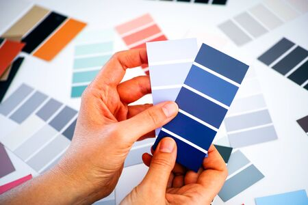 Woman hands choosing blue colour in sample palettes. Close-up.