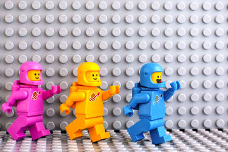Tambov, Russian Federation - June 04, 2020 Three Lego astronaut minifigures going one after another on gray baseplate background. The LEGO Movie 2.