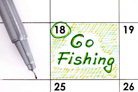Reminder Go Fishing in calendar with pen. June 18