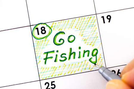 Woman fingers with pen writing reminder Go Fishing in calendar. June 18