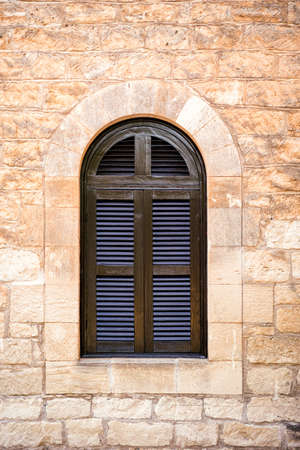 Arched window with closed shutters on yellow stone wall