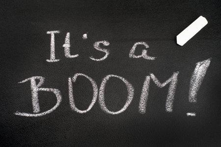 Words It`s a BOOM! written on blackboard with chalks.