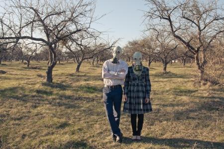 Couple in gasmasks among bare trees photo
