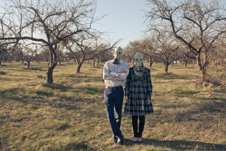 polution: Couple in gasmasks among bare trees Stock Photo