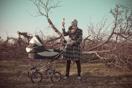 gasmask: Woman in gasmask with kids buggy