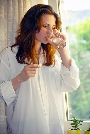 dudando: Mujer sostiene la p�ldora y un vaso de agua
