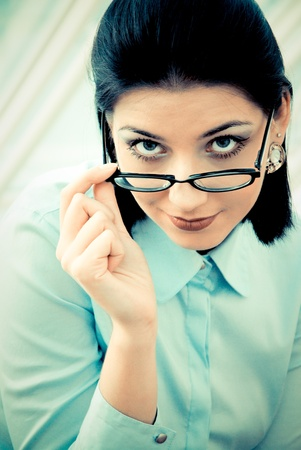 Serious business woman looking over spectacles Stock Photo - 13785493