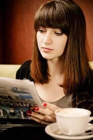 Young woman reading newspaper photo