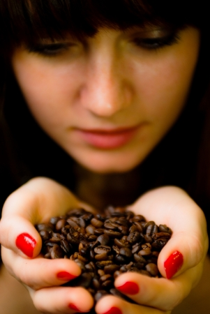 Young woman smelling coffee beans closeup photo