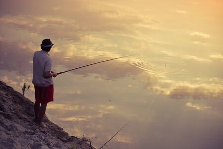 Man fishing in sky reflection Stock Photo