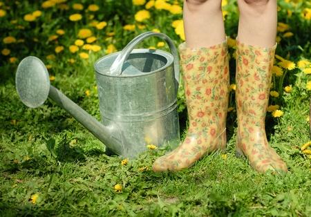 Waterpot en rubber laarzen op de achtergrond van groen gras en paardebloem
