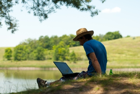 river bank: Man with laptop on river bank