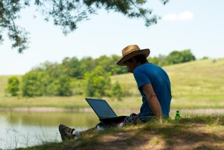 freiberufler: Mann mit Laptop am Ufer des Flusses Lizenzfreie Bilder
