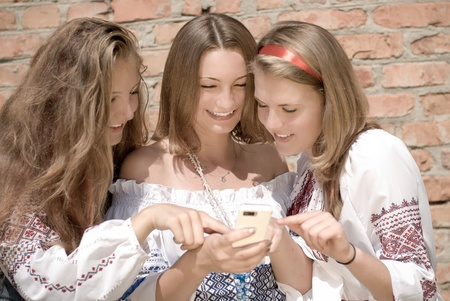 Three happy teen friends looking on mobile phone photo