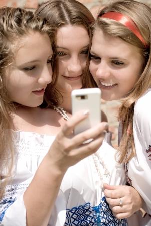 Three friends looking on mobile photo