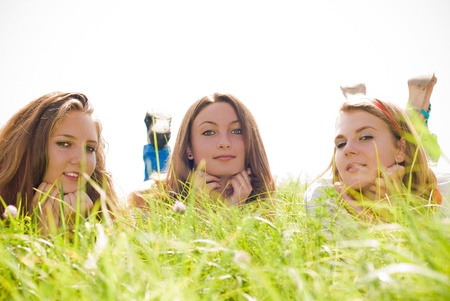 Three teen friends lying in green grass photo