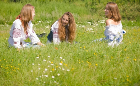 Three teen friends sitting in green grass photo