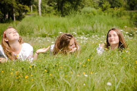 under ground: Three teen friends lying in green grass