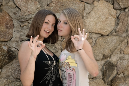 Two teen girls showing okay sign photo