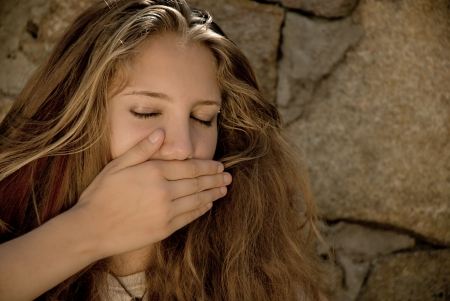 Teenage girl showing silence sign photo