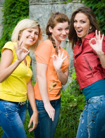 Three women showing okay gesture photo