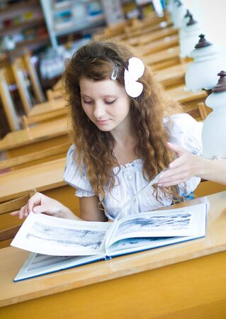 Young pretty female student in library photo