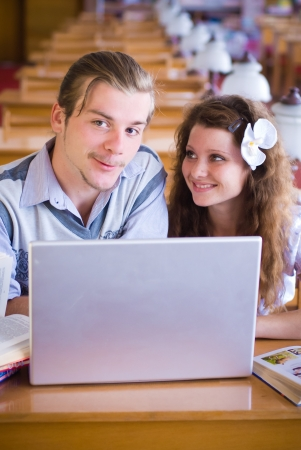 Happy students with laptop in library photo