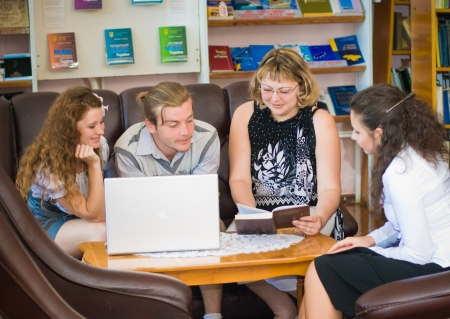 Students sitting in library working together photo