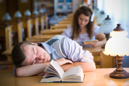 Young student sleeping tired in library photo