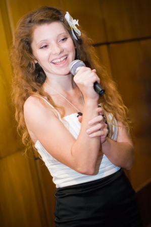 Young happy woman singing in karaoke photo