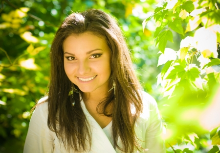 Young happy pretty lady smiling among green leaves  photo