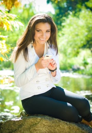 Young beautiful woman texting message in park photo
