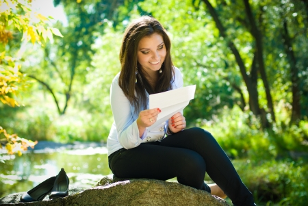 Young beautiful woman reading good news in park