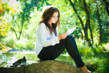 dark haired woman: Young beautiful woman reading good news in park