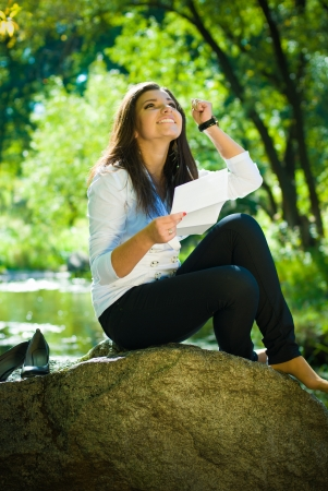 Young beautiful woman reading good news in park photo