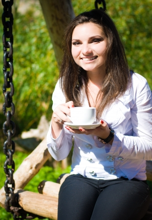 Young pretty woman drinking coffee outdoors photo