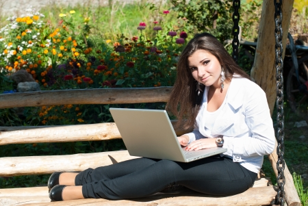 Happy young woman with laptop outdoors photo