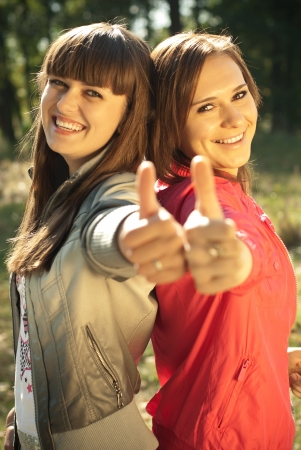 Two happy female friends showing okay sign photo