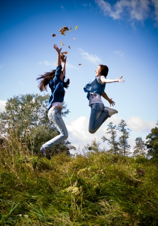 Two happy female friends jumping against blue sky Stock Photo