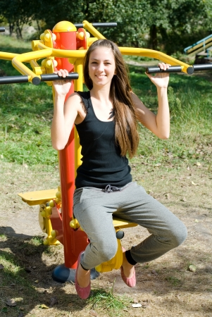Girl training on muscle builder Stock Photo - 13785932