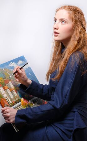 Redhaired girl painting landscape picture photo