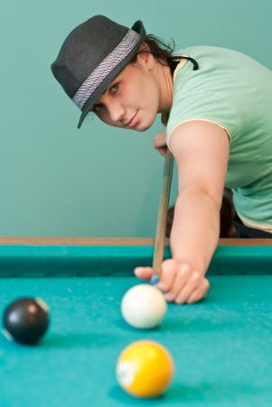 Young pretty woman playing billiards photo