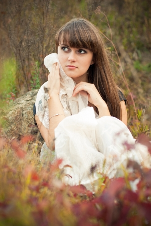 Young beautiful woman sitting among autumn flowers photo