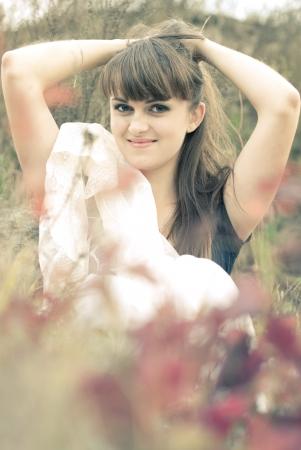 Young beautiful woman sitting among autumn flowers photo