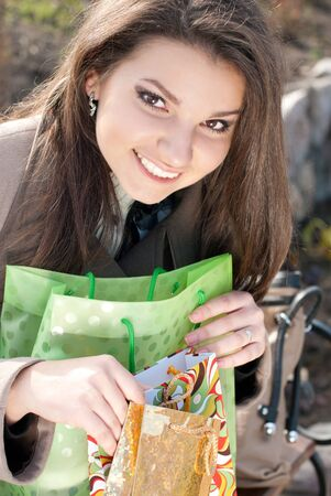 Young happy woman with shopping bags checking purchases photo