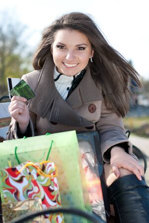 Young happy woman with shopping bags and credit card outdoors photo
