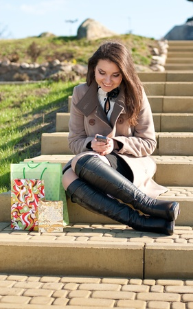 Young beautiful woman sitting on stairs and reading phone message photo