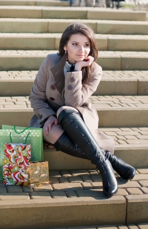 knee boots: Young beautiful woman sitting on stairs and waiting Stock Photo