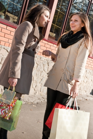 Two young pretty women with shopping bags and talking photo