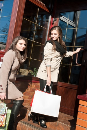 Two young pretty women entering shop photo